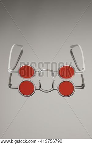 Red Round Glasses In White Frame On Mirror-gray Background. Creative And Fashionable Glasses.