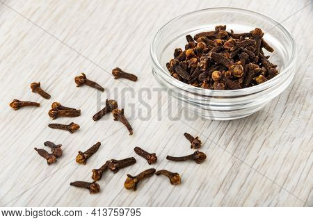 Scattered Clove Spice, Clove Spice In Transparent Glass Bowl On Wooden Table