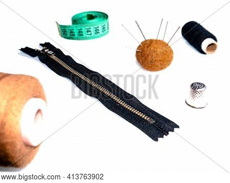 Knitted Zipper And Sewing Accessories On A White Background. Knitted Zipper. Needles And Threads. Se