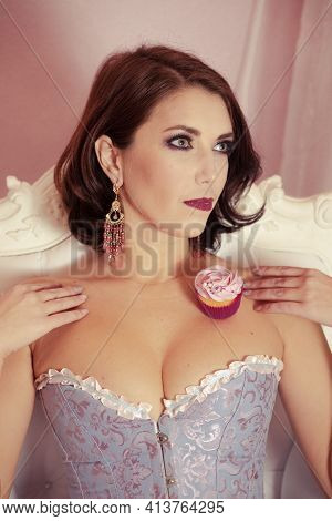 Woman On A White Expensive Chair And A Mouthwatering Cupcake On Her Shoulders In A Deep Neckline Dre