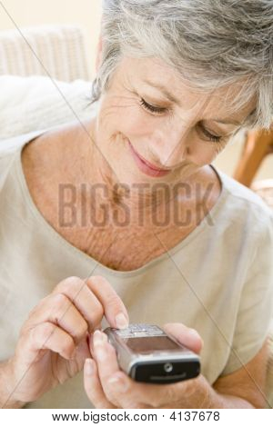 Woman Using Cellular Phone Indoors Smiling