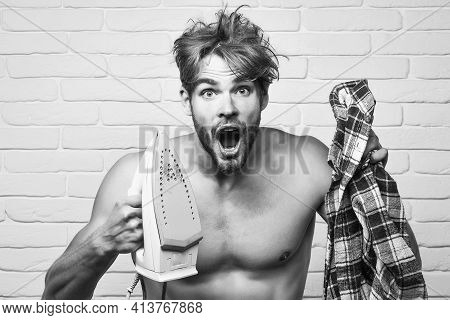 Naked Screaming Man With Iron. Young Handsome Topless Man With Messy Hair Screams And Plaid Shirt