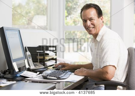 Man In Home Office At Computer Smiling