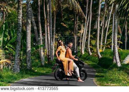 A Happy Young Couple Rides A Scooter Among The Palm Trees. A Beautiful Young Couple Is Traveling On