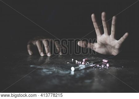Human Hand Trying To Reach,  On  Concrete Floor. Drugs Addiction And Withdrawal Symptoms Concept. Dr