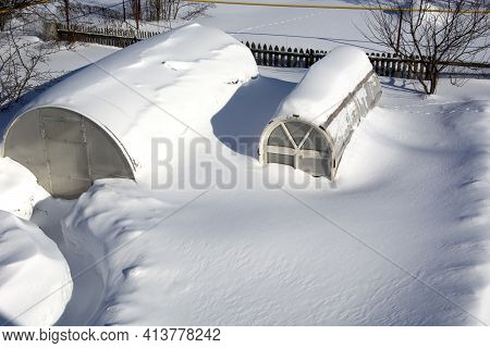 Huge Drifts Of Snow At Their Summer Cottage. Snow Covered Vegetable Garden In The Countryside. The G