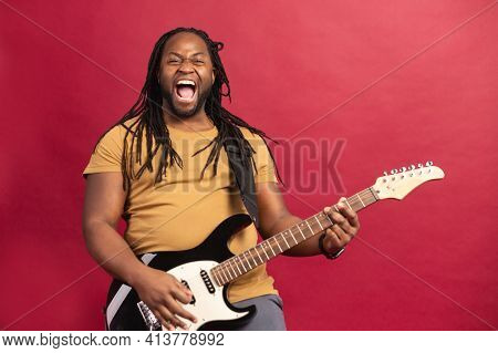 Smiling Energetic And Enthusiastic Young African American Male Musician With Dreadlocks Playing Guit