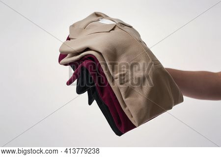 Male Hand Holding Basic Multi Colored T-shirts Against Grey Background. Casual Clothes For Men And W