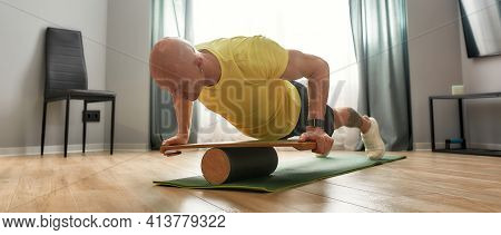 Sportive Middle Aged Caucasian Man Exercising On Balance Board While Doing Push Ups In Light Room, P