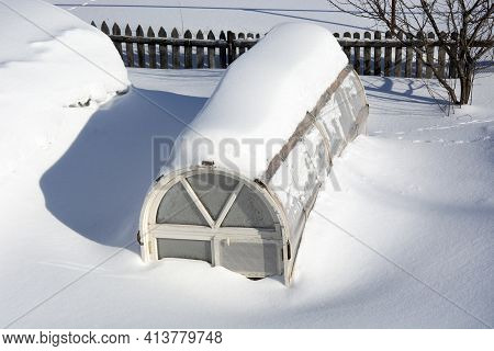 Snow Covered Vegetable Garden In The Countryside. Summer Cottages In The Snow. The Greenhouses Are C