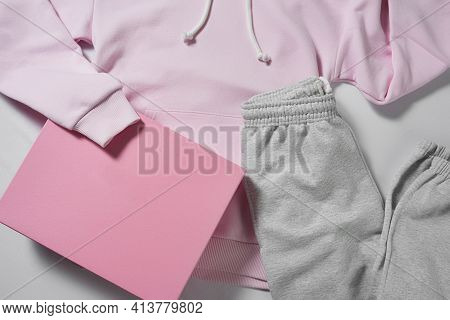 Casual Clothes For Women On Grey Background, Pink Hoodie And Grey Sports Pants. Fashion And Basic We