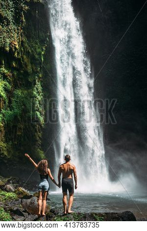 Couple At The Waterfall, Rear View. Couple On Vacation In Bali. Honeymoon Trip. A Couple In Love Tra