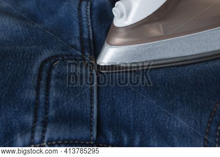 The Process Of Ironing Jeans With An Iron. Iron Spout Close-up On Denim. Routine Household Duties Of