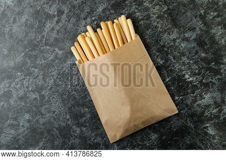 Paper Bag With Grissini Breadsticks On Black Smoky Background