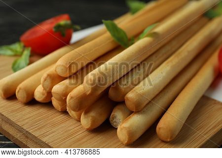 Board With Grissini Breadsticks On Wooden Table, Close Up
