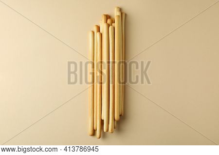 Tasty Grissini Breadsticks On Beige Background, Space For Text