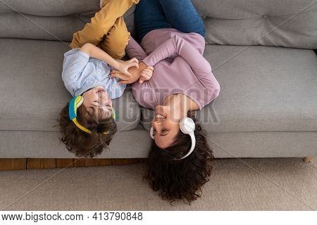 Smiling Happy Mother And Kid Son Lying Upside Down On Couch At Home, Laughing, Tickling Each Other H