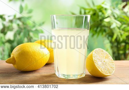 Freshly Squeezed Lemon Juice In Glass On Wooden Table