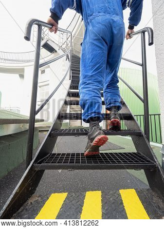 Worker On Staircase. Low Angle View Of Industrial Man Engineer Climbing Up On Steel Stairs In A Fact