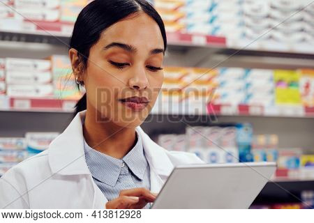 Portrait Of Young Woman In Labcoat Using Digital Tablet In Pharmacy