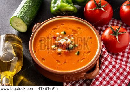 Gazpacho Soup In Crockpot And Ingredients On Black Slate Background. Typical Spanish Food