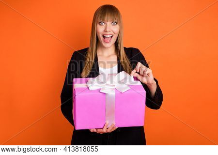 Portrait Of Pretty Amazed Cheerful Girl Holding In Hands Opening Giftbox Isolated Over Bright Orange