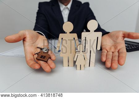 Broker Holds A House Keys. Wooden Figures Of A Family Ahead. Mortgage And Purchase House Concept