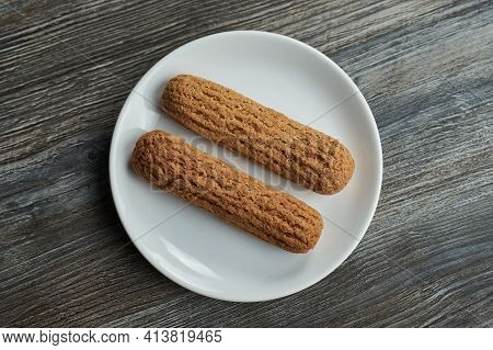 Two Eclairs On A White Plate On A Gray Wooden Table. View From Abovetwo Eclairs On A White Plate On