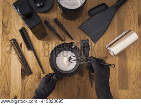 Womens Hands In Black Gloves Hold A Bowl Of Paint And Prepare Tools For Hair Dyeing. Accessories On