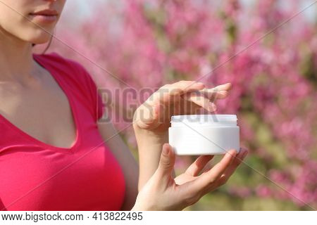 Close Up Of A Woman Hands In Pink Holding Moisturizer Cream Outdoors In A Field