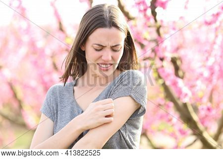 Stressed Woman Scratching Itchy Arm After Insect Bite In A Field Of Peach Trees In Spring Time
