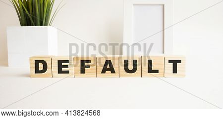Wooden Cubes With Letters On A White Table. The Word Is Default. White Background With Photo Frame,