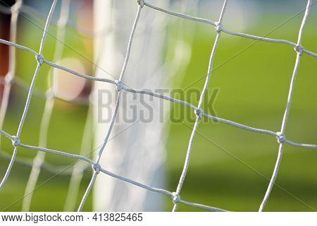 Soccer Football Equipment. White Soccer Net On A Goal. Soccer Net Nodes. Blurred Goal Post In The Ba