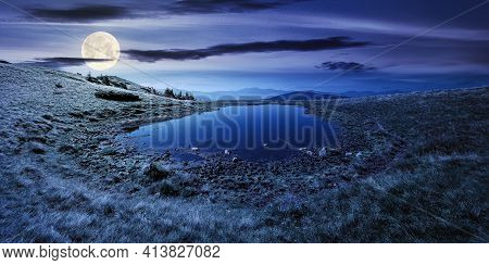 Pond On The Mountain Meadow At Night. Wonderful Summer Landscape In Full Moon Light. Grass And Trees