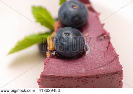 Slice Of  Baked Vanilla And Berries Flavour Cheesecake Swirled With Blueberry Sauce On A Digestive B