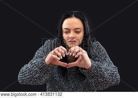 Teenager With Long Dark Hair Making Heart Shape Hand Gesture And Looking At Camera, Isolated On Blac