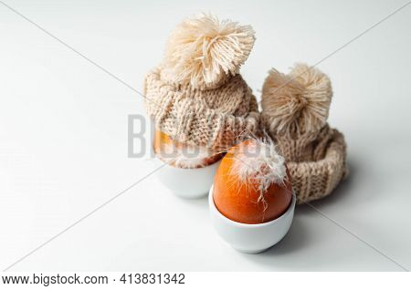 Fresh Free Range Eggs With Natural Feathers In Egg Cups, Eggs In Woolen Caps