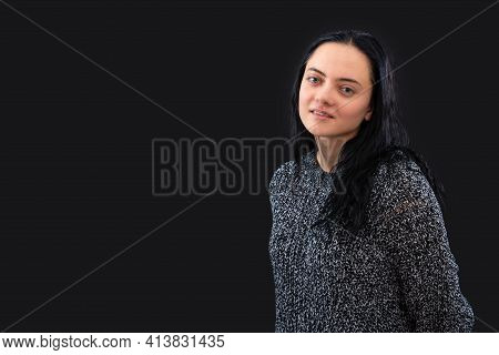 Portrait Of Young Female With Long Dark Hair Wearing Gray Knitted Sweater Over Black Background