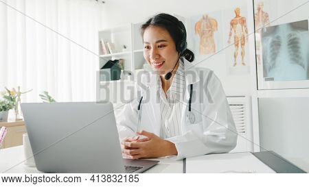 Young Asia Lady Doctor In White Medical Uniform With Stethoscope Using Computer Laptop Talking Video