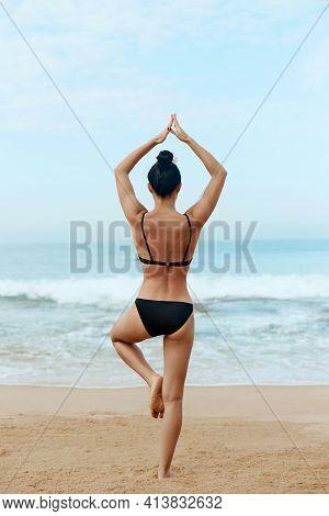 Beautiful Woman Practices Yoga And Meditates On Th Ebeach. Girl Doing Yoga.  Active Lifestyle. Healt