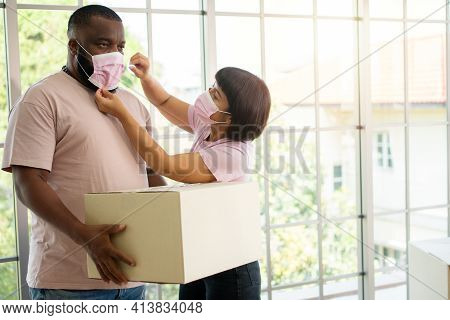 Mixed Race Couple American African And Asian A Surgical Mask Is Carrying Cardboard Boxes In A New Ho