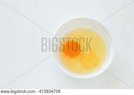 Raw Broken Chicken Eggs. Egg Yolks In A White Plate