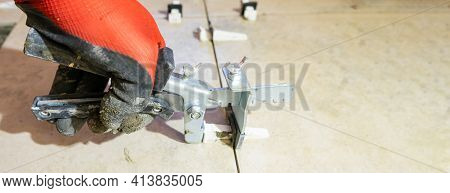 A Worker Is Leveling The Ceramic Tile With Wedges And Clips. Tile Leveling System. Banner.