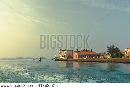 The Bright Rays Of The Rising Sun Illuminate Residential Buildings Located On The Very Coast Of The