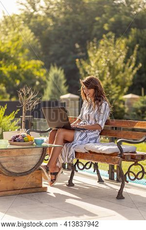 Female Freelancer Working On Laptop Computer, Drinking Coffee And Enjoying Sunny Summer Day Outdoors