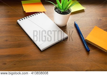 Workplace Concept. The Flower, Notebook And Stickers Are Located On The Surface Of The Writing Table