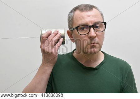 Portrait Of A Man Using And Listening A Tin Can Phone