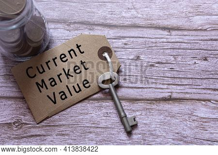 Text On Brown Tag With House Key And Blurred Jar Full Of Coins On Wooden Table - Current Market Valu