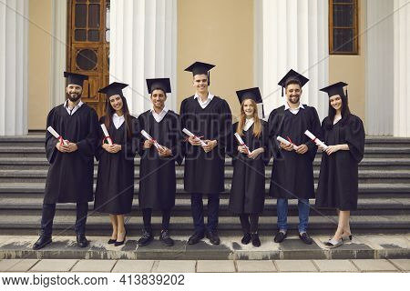 Group Of Graduates In Academic Dresses Posing With Diplomas Against The Background Of The University