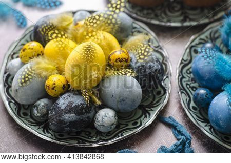 Painted Eggs On The Easter Table With Feathers